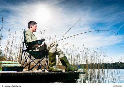 Bild vergrößern: Man fishing at lake sitting on jetty close to the water