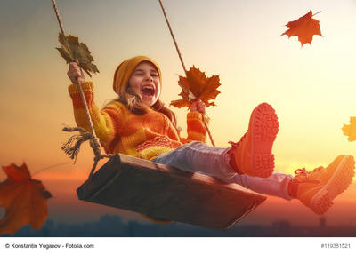 Bild vergrößern: Happy child girl on swing in sunset fall. Little kid playing in the autumn on the nature walk.